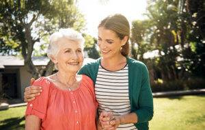 A woman puts an arm around her elderly mother.