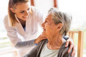 A nursing home worker smiles with an elderly woman in her care.